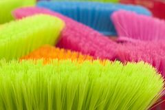Close-up view brightly colored brooms. Macro of colorful street brooms at a market in pink, blue and green Royalty Free Stock Photography