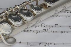 Macro colpo della flauto su partitura Immagine Stock