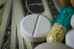 Macro colpo delle pillole su un mucchio dei dollari immagine stock