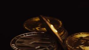 Macro colpo di litecoin luminoso e di rotazione dorata dei bitcoins archivi video
