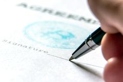 Macro. The concept of the contract of purchase for bitcoin. A ballpoint pen in the person`s hand on a piece of paper with a bit-c stock photo