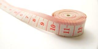 Macro conceptual simples, ilustra??o para controlar algo, alfaiate pl?stico cor-de-rosa Meter no fundo branco fotos de stock royalty free