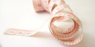 Macro conceptual simples, ilustra??o para controlar algo, alfaiate pl?stico cor-de-rosa Meter no fundo branco imagens de stock royalty free