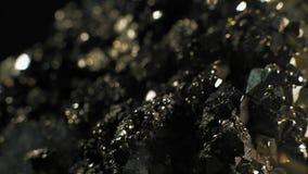 Macro, cristalli brillanti di Pirita su un fondo nero stock footage