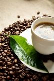 Macro cropped shot of frothy coffee with green leaf on linen cloth Royalty Free Stock Images