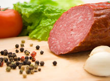 Macro of cut salami, pepper seeds and vegetables Stock Images