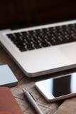 Macro détail de lieu de travail avec l'ordinateur portable ouvert, le téléphone intelligent, le stylo et le carnet Image libre de droits