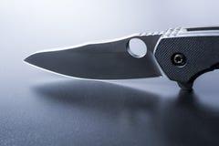 Macro d'une lame d'un couteau militaire ouvert qui se tient sur la terre foncée Photos stock