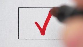 Macro da mão que tira a marca de verificação vermelha no papel com marcador video estoque