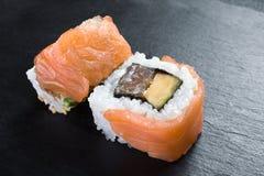 Macro de deux petits pains de sushi japonais d'un plat noir Photographie stock libre de droits