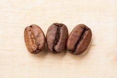 Macro de feijões de café no fundo de madeira imagem de stock royalty free