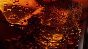 Macro de la cámara lenta tirada de los cubos de hielo en un vidrio de cola metrajes