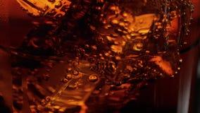 Macro de la cámara lenta tirada de los cubos de hielo en un vidrio de cola almacen de metraje de vídeo