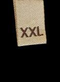 Macro de la escritura de la etiqueta de la ropa de la talla de XXL Foto de archivo