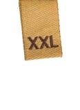 Macro de la escritura de la etiqueta de la ropa de la talla de XXL en blanco Imágenes de archivo libres de regalías