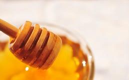 Macro de la miel con el cazo de madera de la miel en el tarro de cristal Fotos de archivo
