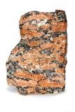 Macro de la roca de grano grueso roja del granito aislada en el fondo blanco foto de archivo