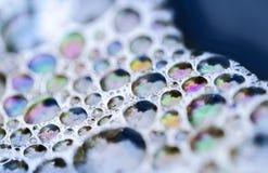 Macro de las burbujas de jabón coloridas en el agua Fotos de archivo
