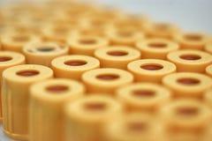 macro de tubos de ensayo con el top amarillo, contra una pendiente del fondo blanco Foco selectivo fotos de archivo libres de regalías