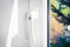 Macro de um punho de janela Lockable de uma janela branca fechado com as árvores no fundo imagem de stock