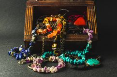 Macro de uma caixa de madeira e de umas joias coloridas Fotos de Stock