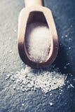 Macro de uma pá de madeira da cozinha com sal branco da grão na pedra da ardósia, Front View imagens de stock