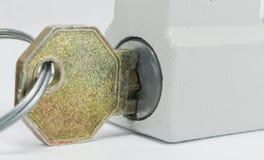 Macro de un candado bloqueado con la llave Imagenes de archivo