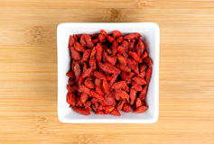 Macro of dehydrated red goji berries in white bowl Stock Image