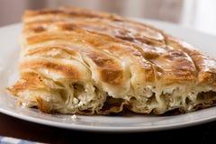 Macro del primer del burek balcánico con queso en la placa Foto de archivo
