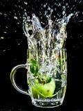 Macro del primer del chapoteo del agua de la manzana Fotos de archivo libres de regalías
