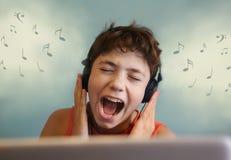 Macro del primer de un adolescente masculino que escucha la música con el auricular Foto de archivo