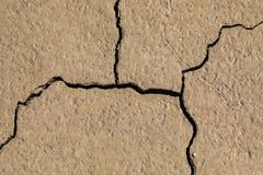 Macro del primo piano di terra fangosa incrinata su un letto di lago fotografia stock