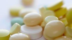 Macro des pilules, des Tablettes, des capsules médicales et des drogues tombant au fond blanc clips vidéos