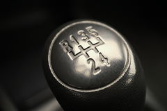 Macro detail of a black knob of a used manual shift gear (gear stick) in the aged vehicle Royalty Free Stock Photography