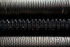 Macro detail of black and silver head of a shaving machine with its sharp razor blades behind the perforated metal grid. Macro detail of a black and silver head stock photo