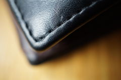 Macro detail of a black thread stitching black and brown stitched leather wallet Stock Images