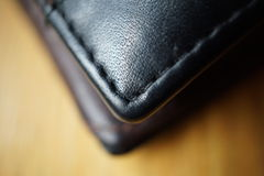 Macro detail of a black thread stitching black and brown stitched leather wallet Stock Photo