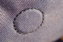 Macro detail of a circle made of stitched thread on the glossy fabric Royalty Free Stock Image