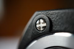 Macro detail of a cross-shaped metal connecting opposite parts of the plastic headphones Royalty Free Stock Photo