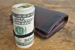 Macro detail of a green roll of American currency USD, American dollars with 100 dollars bank note next to a leather wallet as a. Macro detail of a green roll of stock image