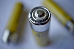 Macro detail of isolated yellow batteries as a symbol of accumulated energy and portable power. Macro detail of three isolated yellow batteries as a symbol of Royalty Free Stock Image