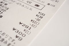 Macro detail of a Japanese paper receipt (white paper bill, sales slip) with a sum of several items Royalty Free Stock Photos