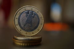 Macro detail of a metal Euro coin on the column created of coins with a positive warm background Stock Photo