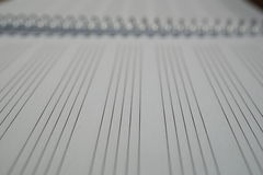 Macro detail of a notepad with paper lined as piano sheet with lines prepared for composing music Stock Images