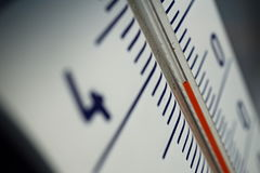 Macro detail of and old dusty outdoor thermometer in the retro design measuring high temperature of thirty five degrees of Celsius Stock Image