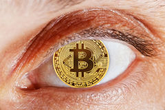 Human eye with coin bitcoin instead of pupil. Macro detail photo of open human eye with coin bitcoin instead of pupil Stock Images