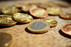 Macro detail of a pile of coins on the wooden surface with a silver and golden Euro coin separated from other metallic coin curre Stock Photos