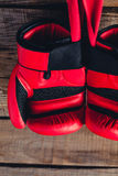 Macro detail of red boxing gloves. Wooden background. Royalty Free Stock Photography