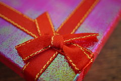 Macro detail of a red ribbon with golden stitching wrapping a pink christmas present Stock Image
