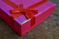 Macro detail of a red ribbon with golden stitching wrapping a pink christmas present Stock Images